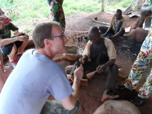 Mr. Deutsch, supervisor of the Benin team's English language teaching mission, harmonizes with a village member using a hand-made metal instrument.