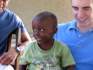 Cadet Jordan Oberlander lets the grandson of loca Tanzanian business woman Carolyn Keesey sit on his lap.