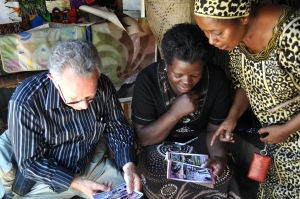 Dr. Thomas Smith and business-woman Carolyn Kessy (standing) review marketing flyers for her business. Kessy wants to better market her tourist shop in the Mwenge market and felt that marketing tools created in English would help her attract the international tourists that frequent the area. Until recent years, female business owners were rare but now considered an integral part of Tanzanian economy. She is the head of a recently created local business association—there is one in each of the five regions of Tanzania.