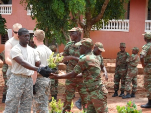 Cadet Emmanuel Nyarko handed off a plant to a Beninese cadet as part of the assembly line transporting the 100 plants purchased for the project into the garden.