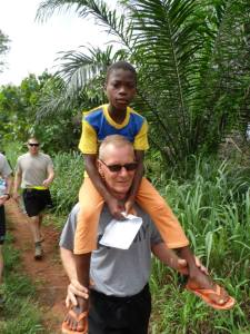 Maj. Weatherlow-- the Benin Team's mission commander, lifts a local Beninese child onto his shoulders as the team hikes to the local medical consultation center