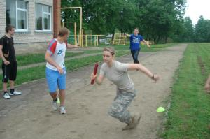 Cadet Hoffman takes off during the relay race, between the Cadets and students at Ariogalos Gimnazija, while the national 100 meter sprint record setter in Lithuania (left) reaches for his team's baton.